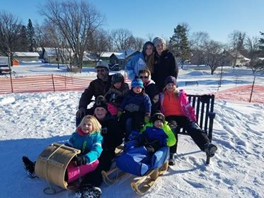 family with wooden toboggan sled and wooden sled