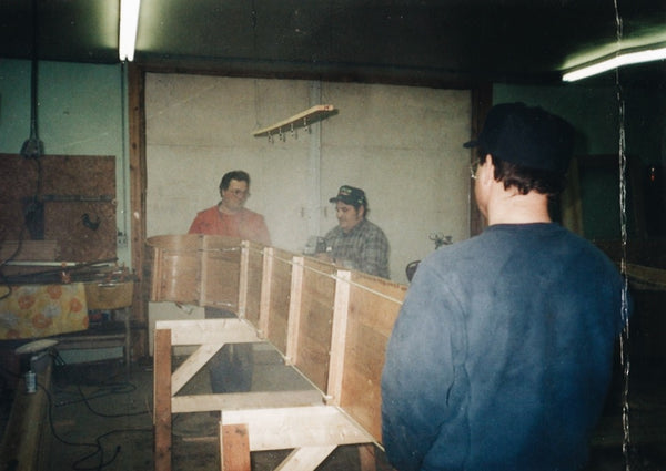 Three men in the workshop, lifting a wood toboggan onto its side