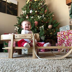 baby on wooden pull sled