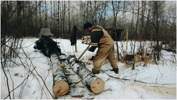 A man in Carhart Overalls, sawing felled aspen beside his Toboggan Sled