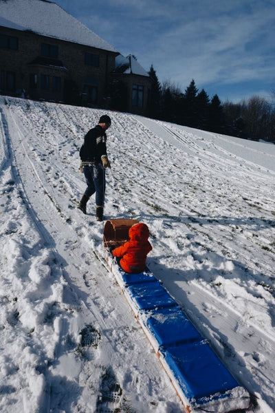 pulling small boy uphill in a downhill sled