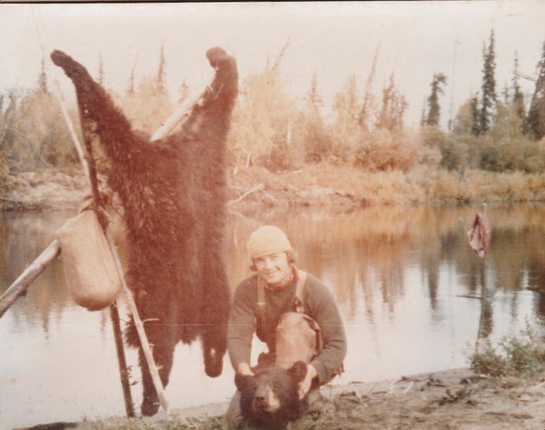 faded photo of young man in tan overalls crouching on a lake. Bearskin strung up behind him