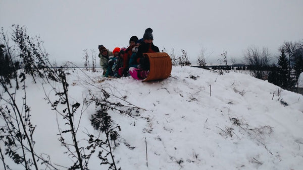 Four kids packed into a toboggan, siting atop a snow-covered hill