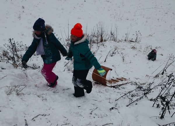 Two girls run up-hill pulling a toboggan sled by the rope