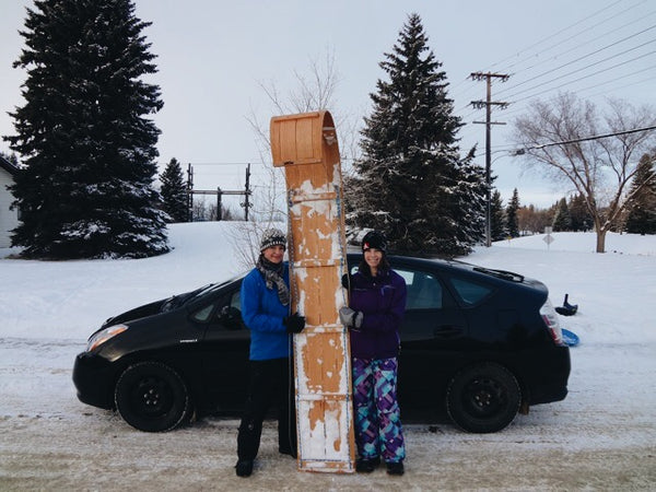 Two women in snowgear hold their upright toboggan sled beside a Toyota prius