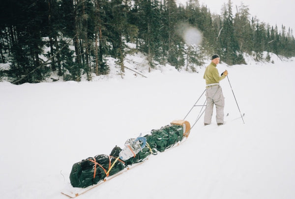 cross country skier, towing a fully loaded hand toboggan