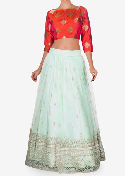Mint blue lehenga with a orange brocade silk blouse embellished in thread work