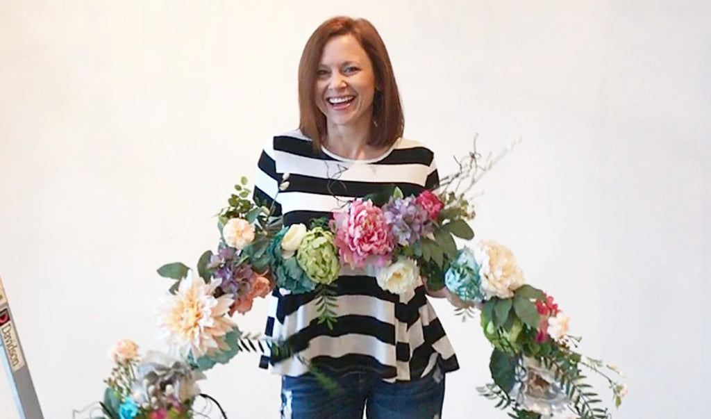 Our Designer, Katy Mimari, holding the finished product before hanging the floral garland on the nursery wall