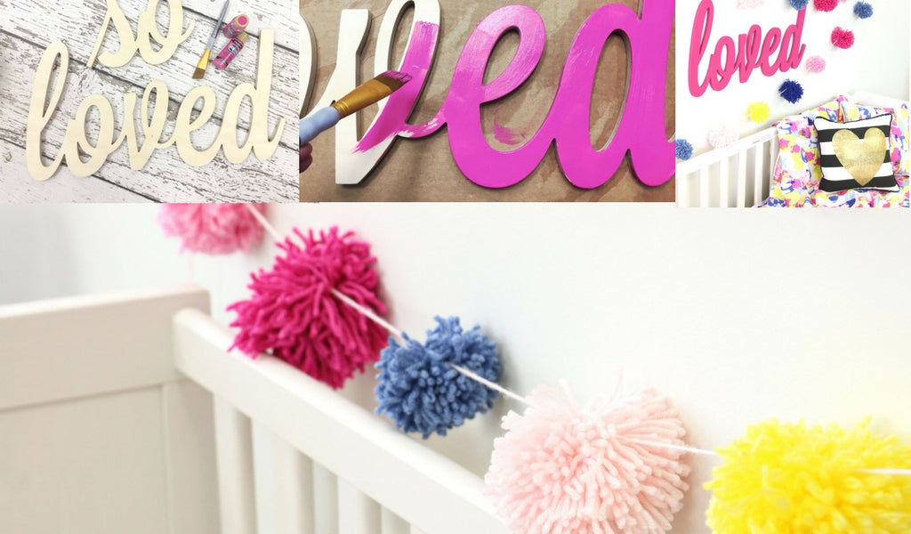 "painted wood saying ""so loved"" with nursery DIY pompom garland"