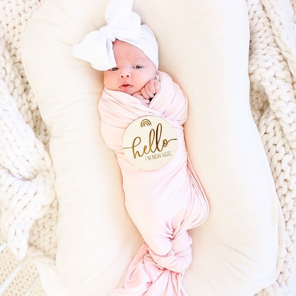 blush swaddle on rust floral crib sheet