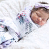 purple floral swaddle on baby