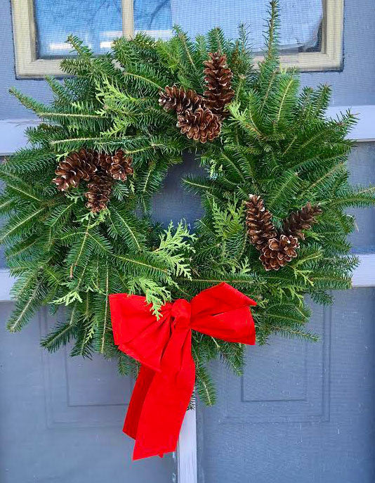 extra full holiday wreath with greens and bow on door