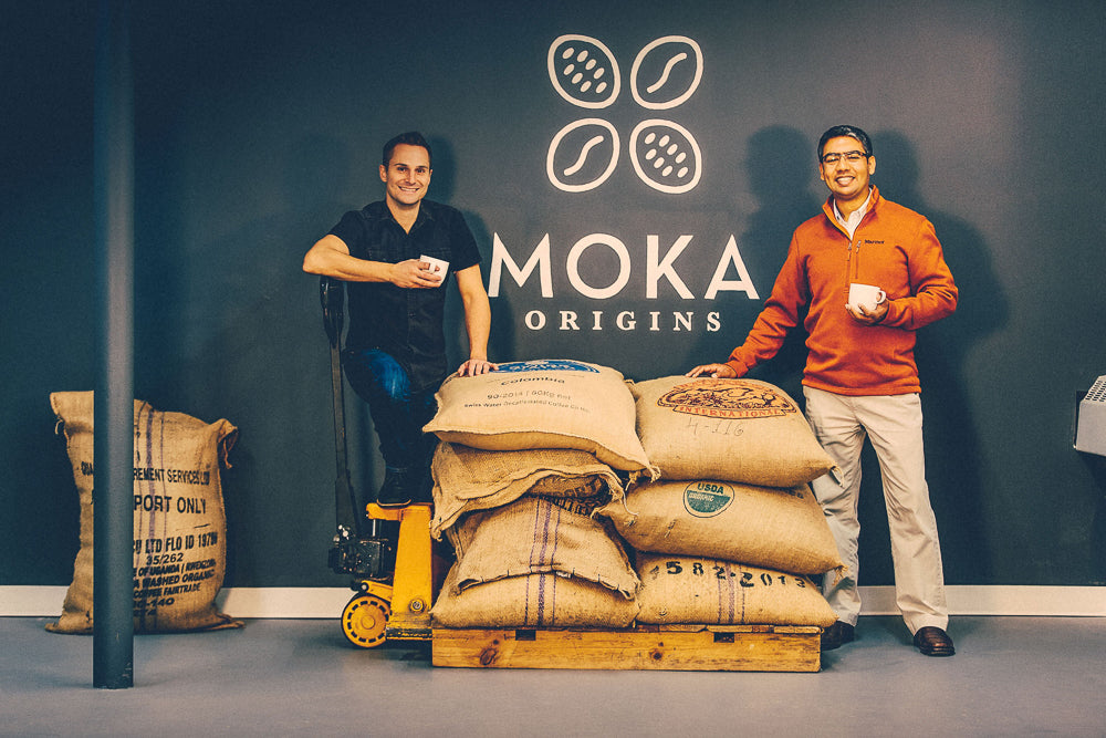 Jeff and Ishan with burlap sacks of cacao and coffee out front of Moka Origins HQ