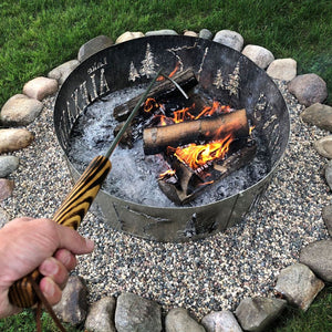 Fire poker being used to move logs in a campfire.