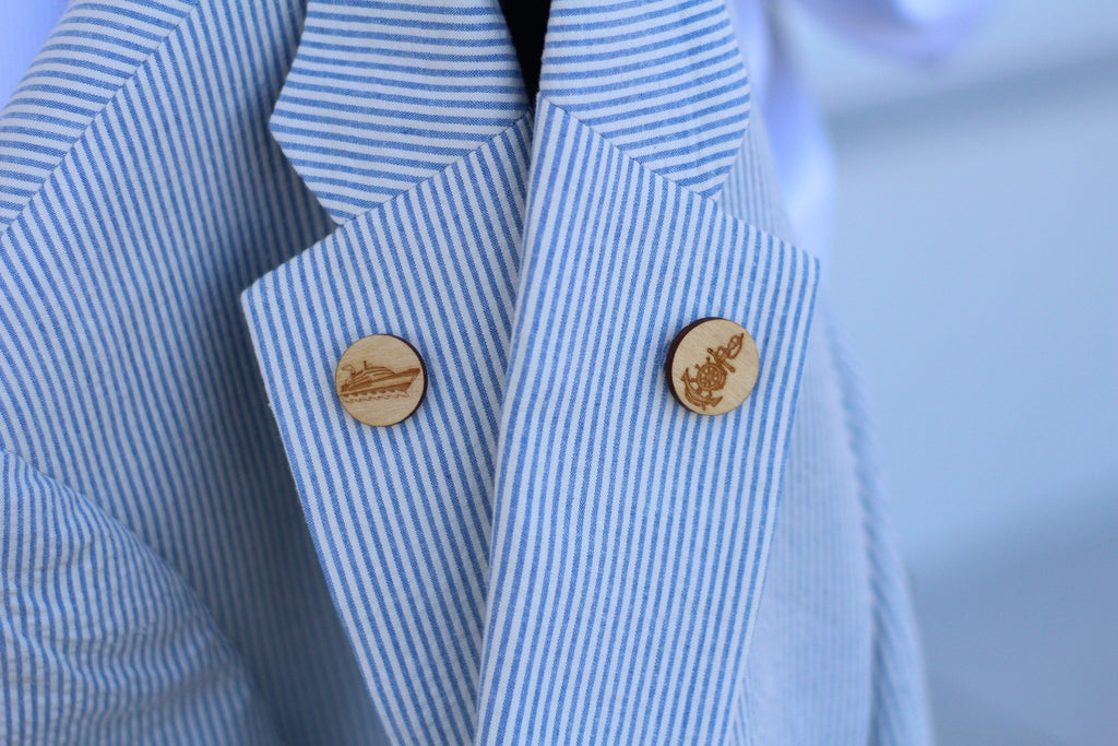 A seersucker jacket with two wooden lapel pins: one boat lapel pin and one anchor lapel pin