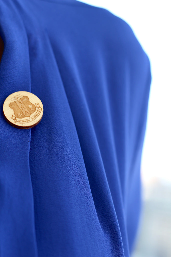Woman Wearing a Greek Alpha Kappa Alpha Sorority Wood Lapel Pin on her blue shirt