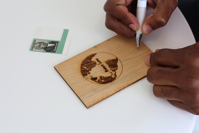Man writing on a wooden card with planet earth engraved on it and an african heritage stamp in the background the words distant lover is written on the card