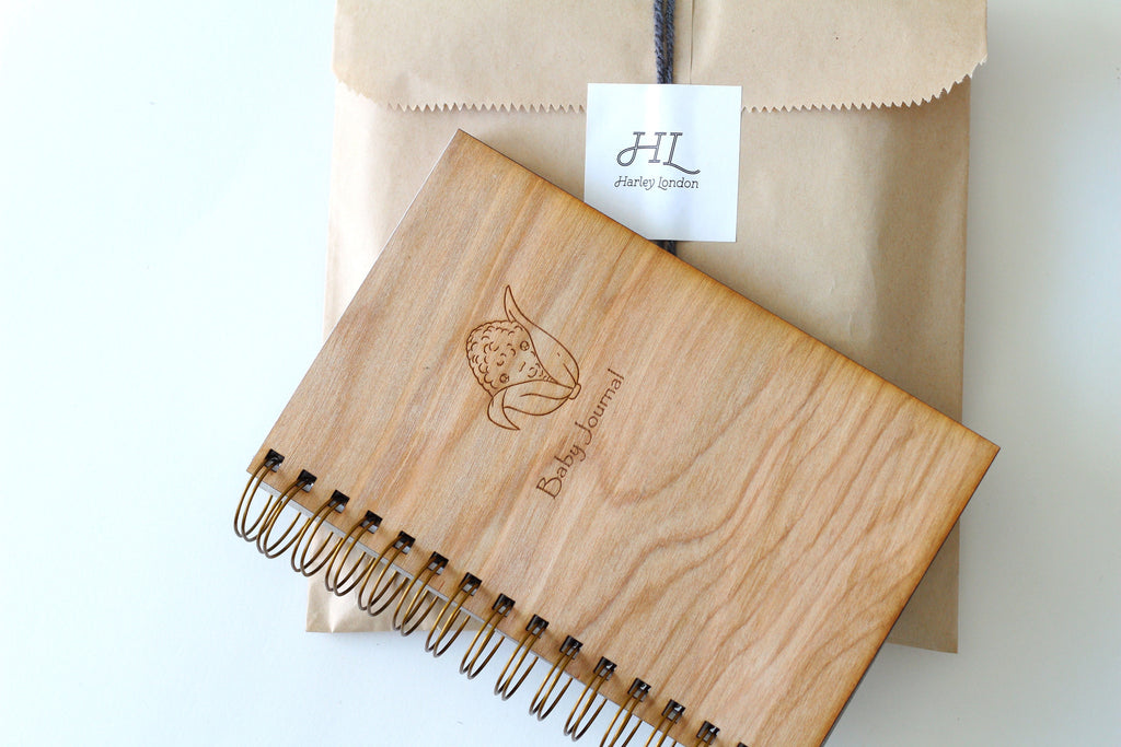 A spiral bound wooden baby notebook with a cute engraved corn drawing on top perfect baby shower guest book
