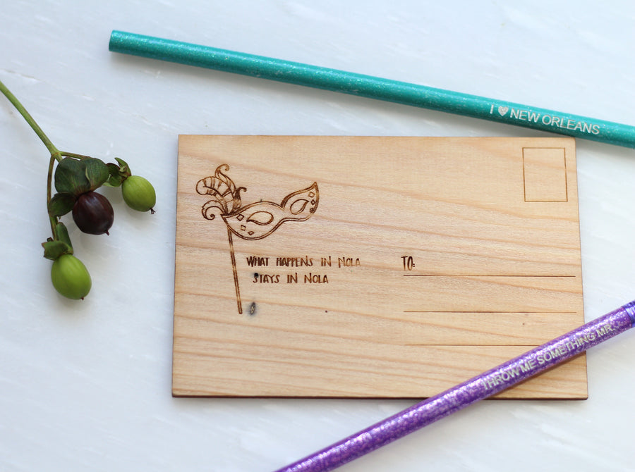 Beautiful Wooden Postcard with Mardi Gras Mask and Feather on it and the words what happens in NOLA stays in NOLA also a pencil that says I love new orleans and mardi gras beads