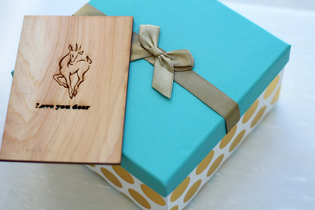 Cute Wooden Deer Greeting Card sitting on decorative turquoise and gold box with gold bow - Made in New Orleans by Harley London