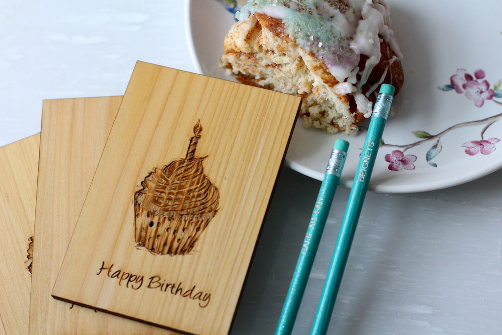 Wooden Happy Birthday Card with a slice of king cake on a small plate and two engraved pencils by Harley London