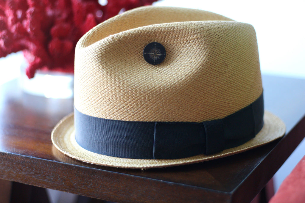 A Black Compass Lapel Pin on a Straw Fedora Hat