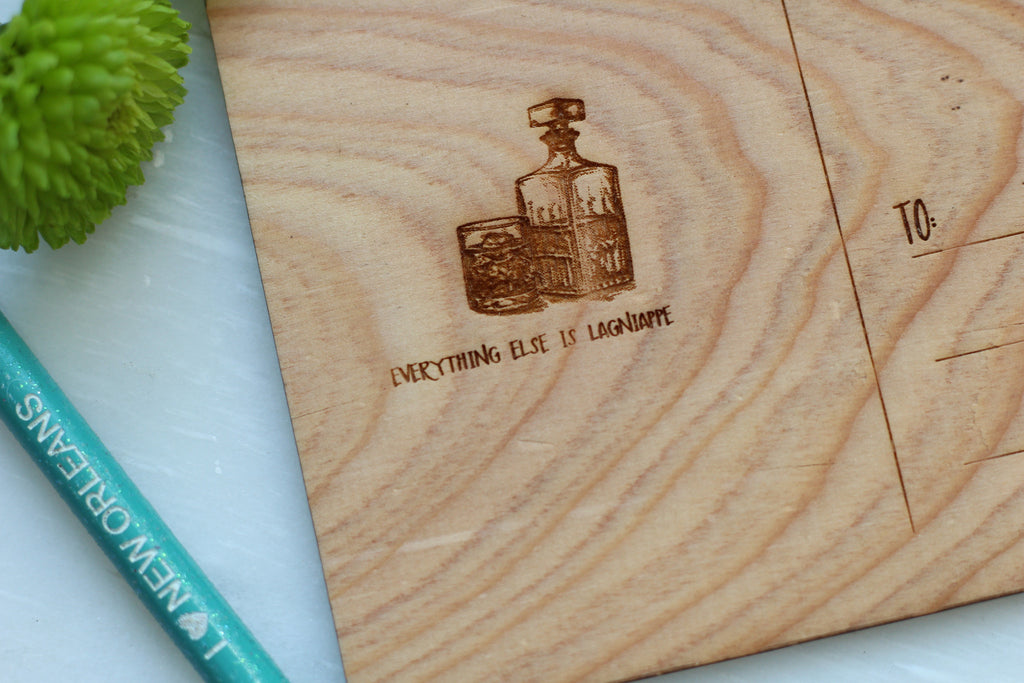 closeup of wooden lagniappe card with bourbon and glass