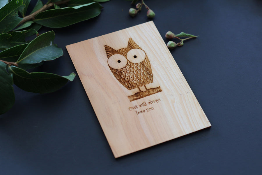 A cute wooden owl postcard lying on a bed of tree leaves and flower buds with the words Owl will always love you written on it