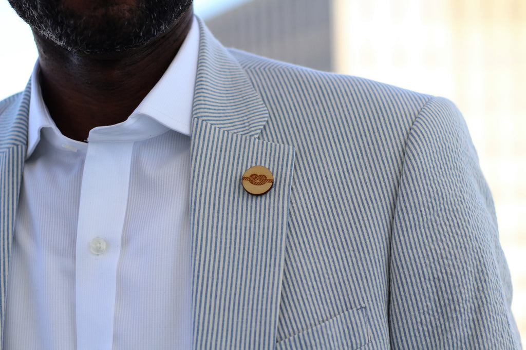 A man Wearing a seersucker jacket with a rope lapel pin