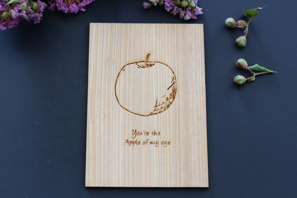 Engraved Wooden Apple Postcard lying on a bed of lilies; apple of my eye is etched on the card