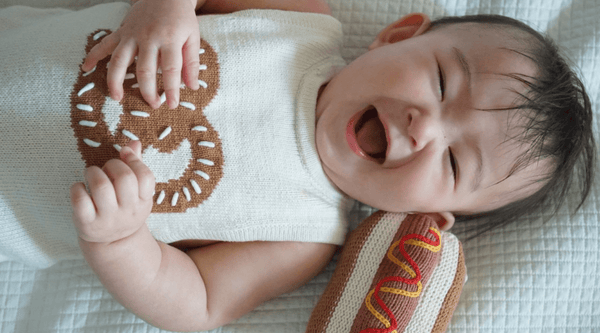 Certified Organic Cotton Baby Toy & Clothe - Picture of newborn with hot dog rattle & wearing knit romper.