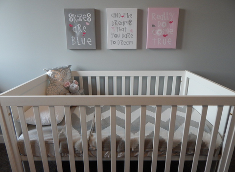 How to decorate - a modern nursery with a white crib, grey wall and art in grey, white and pink.