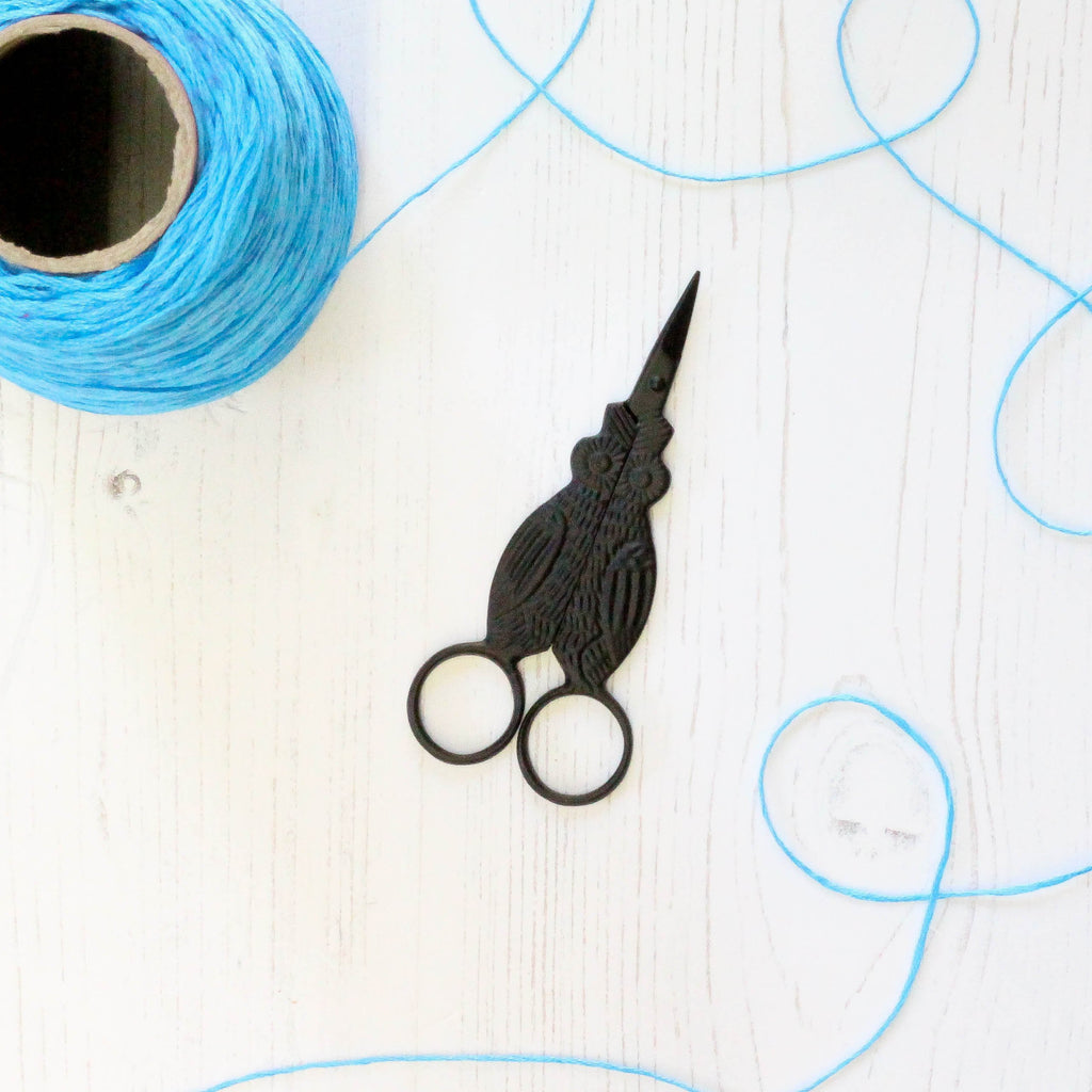 Black Owl Embroidery Scissors closed with thread