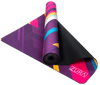 Partially rolled up view of a suede yoga mat covered with lots of pink, yellow, blue, purple, and white stripes angled at 45 degrees with varying widths and lengths. The mat is folded so that both sides are seen.