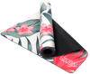 Partially rolled up view of an off-white suede yoga mat with a scattering of pink primrose and lotus flowers and their attached stems and leaves. The mat is folded so that both sides are seen.