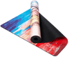 Partially rolled up view of a white yoga mat with painted streaks of red, blue, and yellow and a sketch of a flower adorned elephant head in the center. The mat is folded so that both sides are seen.