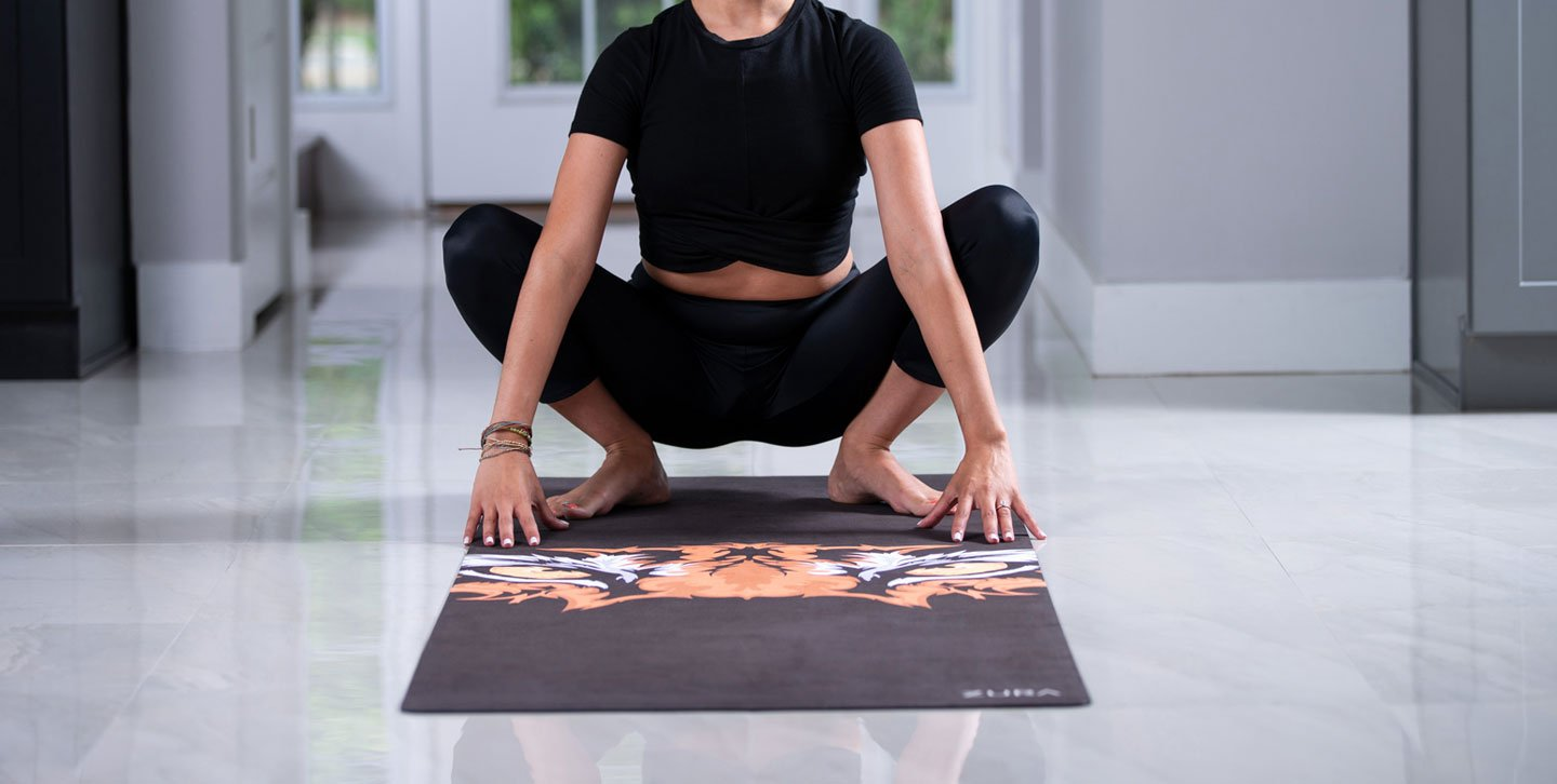 Woman doing Malasana (Garland) pose on a black yoga mat with a tiger face in the center.