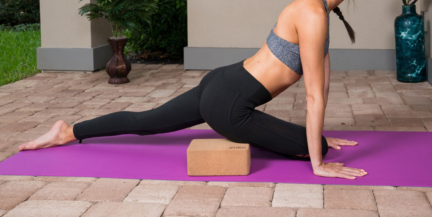 Woman doing Ardha Kapotasana (Half Pigeon) pose using a cork yoga block with rounded edges.