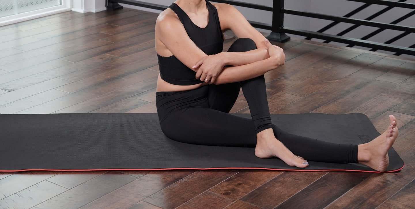 Woman doing Marichyasana C (Seated Twist) pose on a solid black reversible TPE yoga mat.
