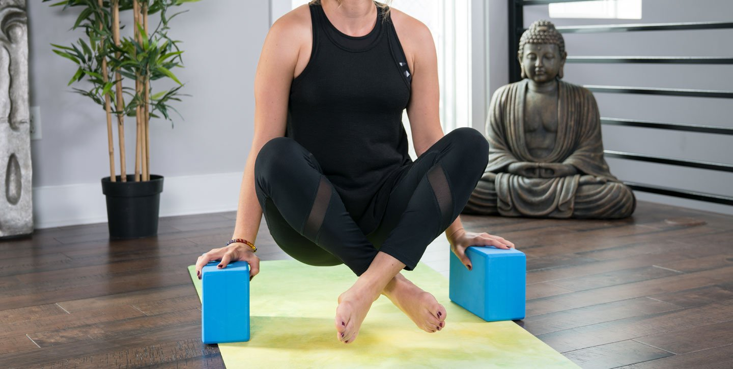 Woman doing Tolasana (Scale) pose using two light blue foam yoga blocks with beveled edges.