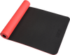 The black side of of a solid red reversible TPE yoga mat, displayed halfway rolled out.
