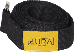 A wide black cotton yoga strap with metal rings and a yellow sewn-on patch featuring the ZURA brand logo, shown rolled up.