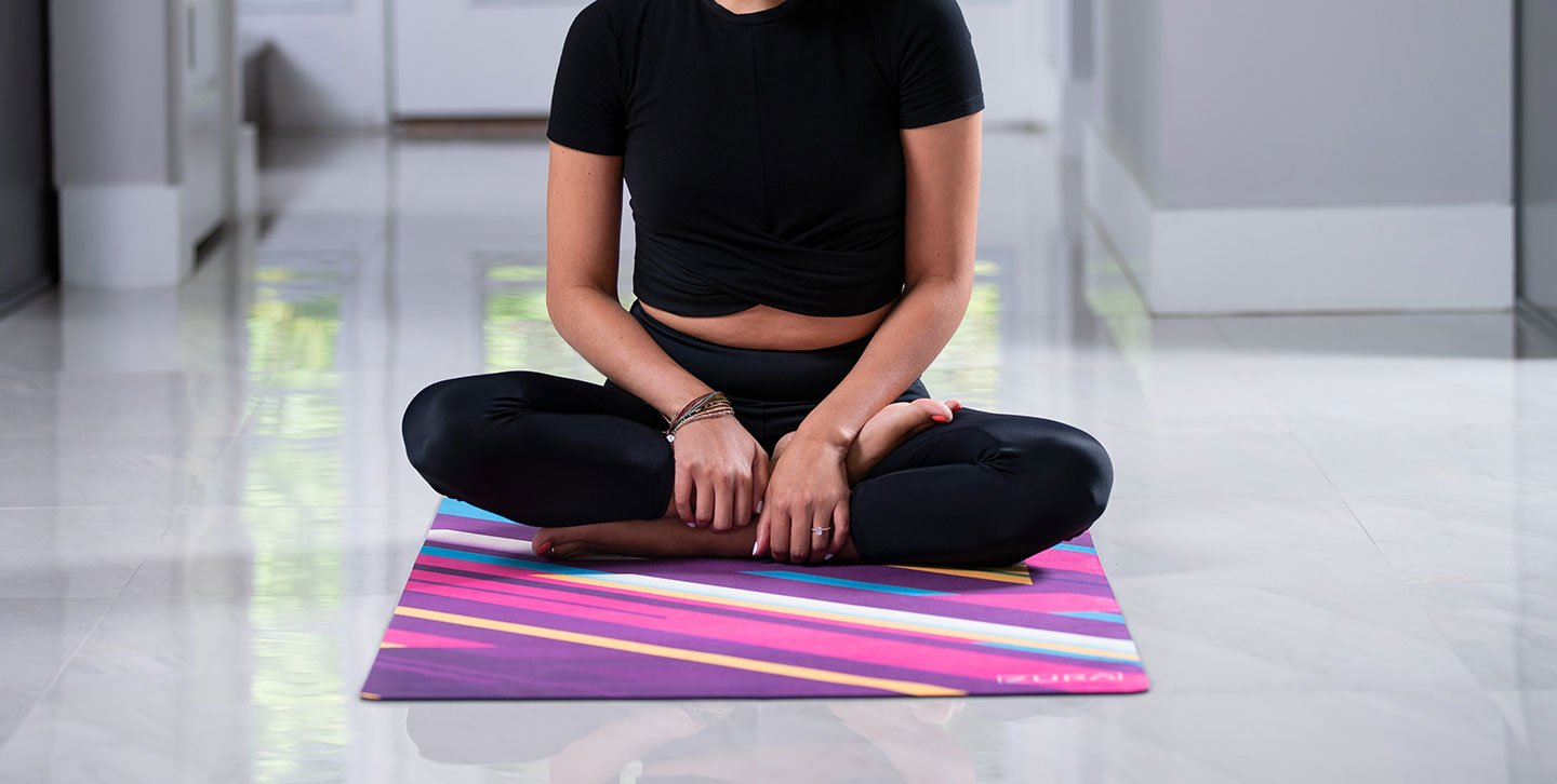 Woman doing Ardha Padmasana (Half Lotus) pose on a suede yoga mat covered with lots of pink, yellow, blue, purple, and white stripes angled at 45 degrees with varying widths and lengths, displayed halfway rolled out.
