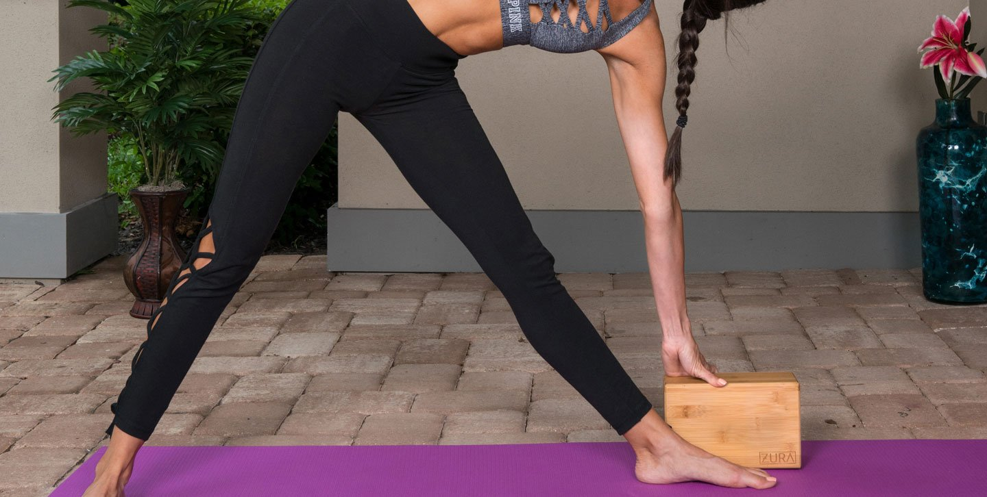 Woman doing Trikonasana (Triangle) pose using a bamboo yoga block with beveled edges.