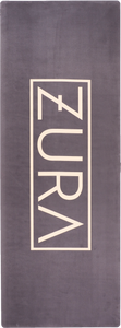 A black yoga mat with a light gold ZURA brand logo in the center.