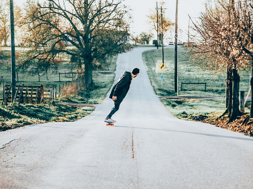 Longboard carving down a winding road