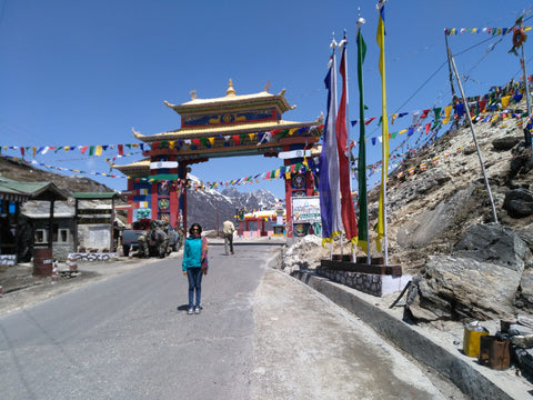 Avantika at the Sela Pass, prayer gate in the background