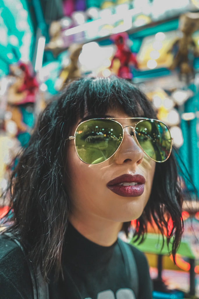 close up portrait women wearing green aviator sunglasses green tint at carnival with lights carnival night colors tones colors funky style goth gothic sunglasses green shades
