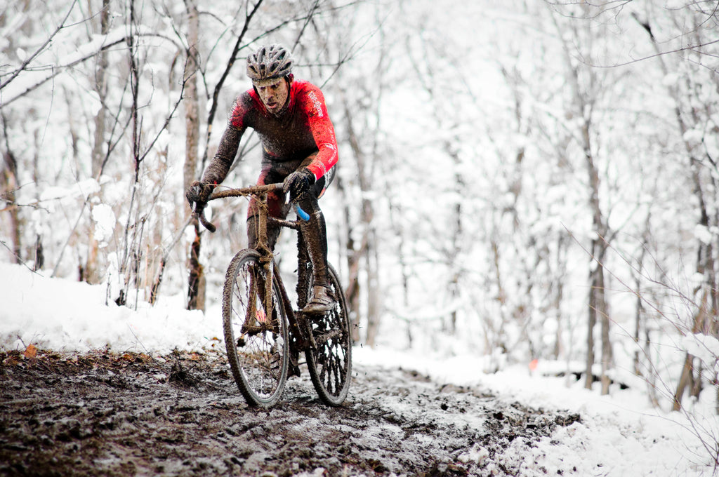 Cyclist riding through the mud during winter