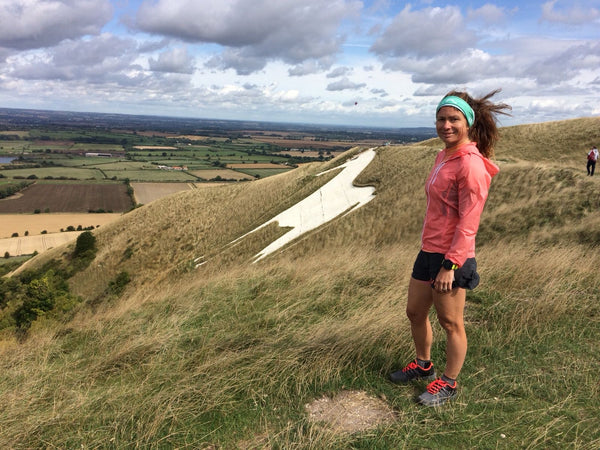 Anna Marie Watson - Ultra marathon runner standing on a mountain and looking at the camera.